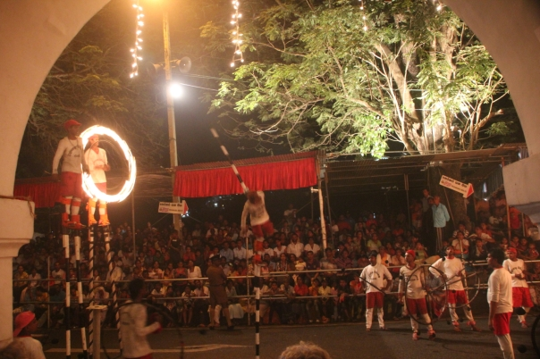 Flame throwers watching a man balancing on one stilt